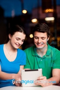 couple-using-tablet-computer-at-an-outdoor-cafe-100275701