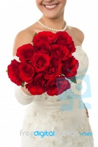 smiling-young-bride-holding-out-a-rose-bouquet-100177942
